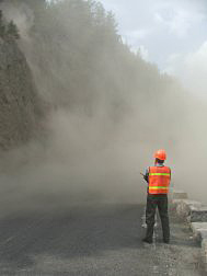 An NPS official stands in front of a dust cloud caused by the rockslide coming off the cliff.