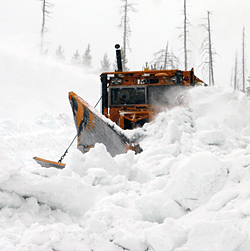 A snowplow plunges through a huge snowbank.