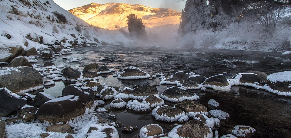 Sunrise peaks over the horizon of a frosty stream.