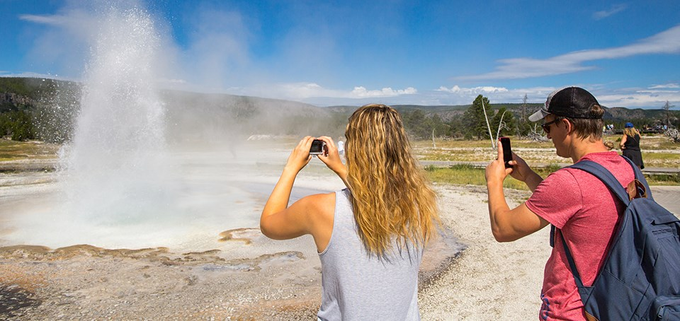 Two people photograph an erupting geyser