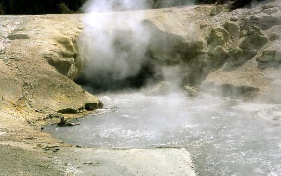 Steam rises from this hot spring which emerges from a small cave.