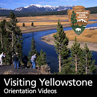 Visitors watching a Hayden Valley scene with the Yellowstone River and distant mountains.