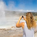 Person photographing an erupting geyser