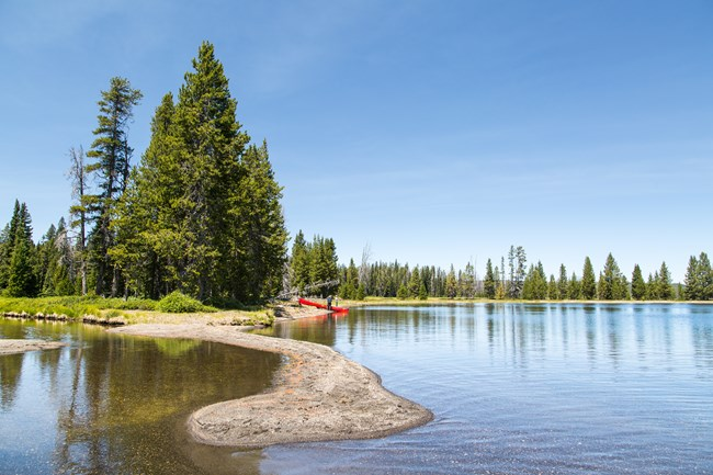Canoeists stand on the shore of Lewis Lake.