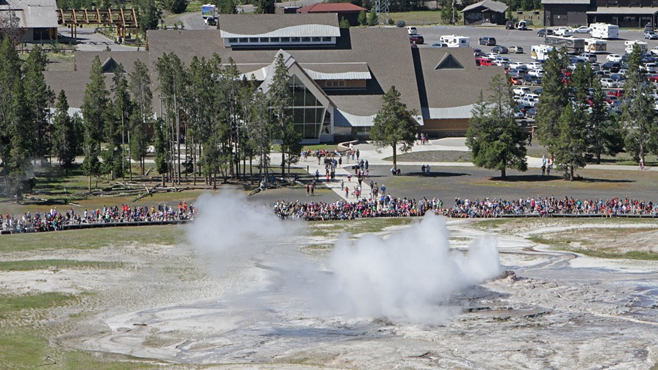 View of Old Faithful Geyser with visitors watching and the Old Faithful Visitor Education Center in the background