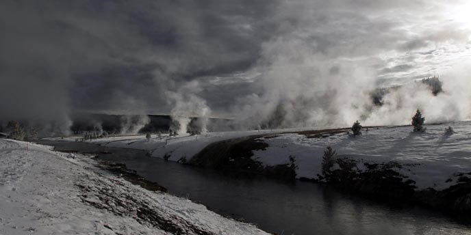 Steam rises from a snow-covered landscape next to a river