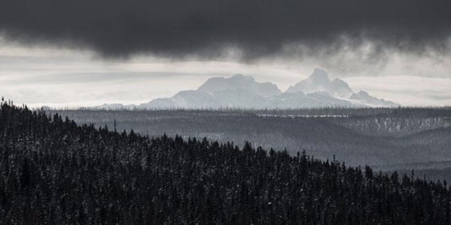 Craggy mountains in the background of snow-dusted forests beneath clouds