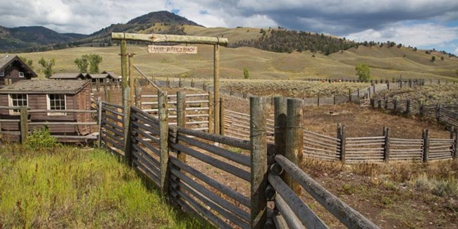 Tall wood fencing leads to the prominent entrance gate to historic cabins