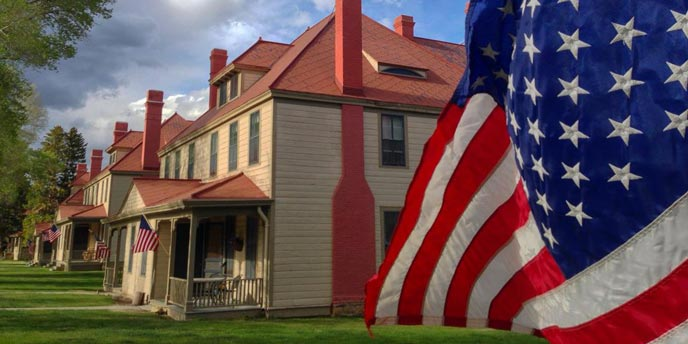 An American flag flies in front of a row of historic buildings