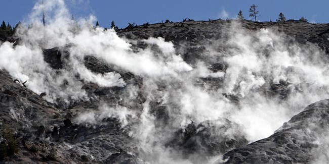 Steam rises from dark black rocks