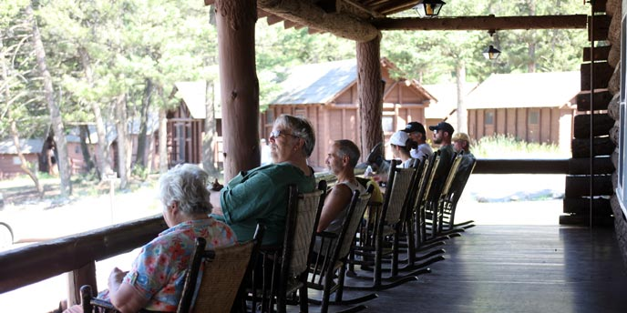 Visitors sit on a rocking chairs on a log porch with cabins in the background