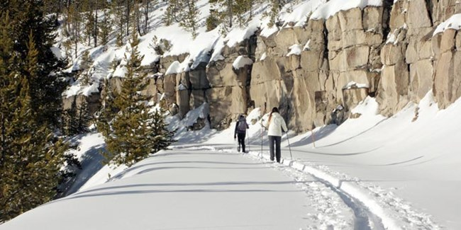 Two people ski in single file along a snow covered road