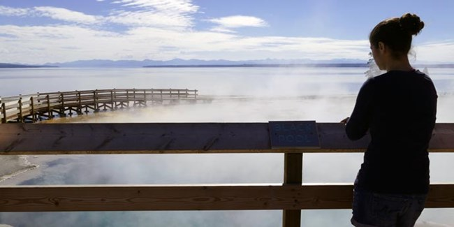 A young woman looks over a steaming pool and a lake from the railes of a boardwalk