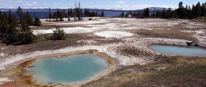 Two hydrothermal pools of water in front of Yellowstone Lake and mountains.