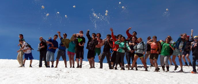 A group of teenagers dressed in warm-weather clothes throw snowballs in the air