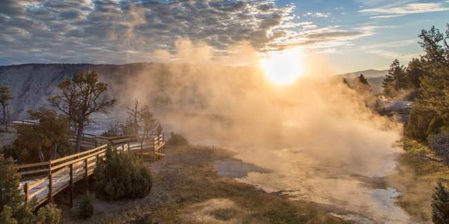 A visitor standing on a boardwalk watches the sunrise through mist rising from the Mammoth Hot Springs.