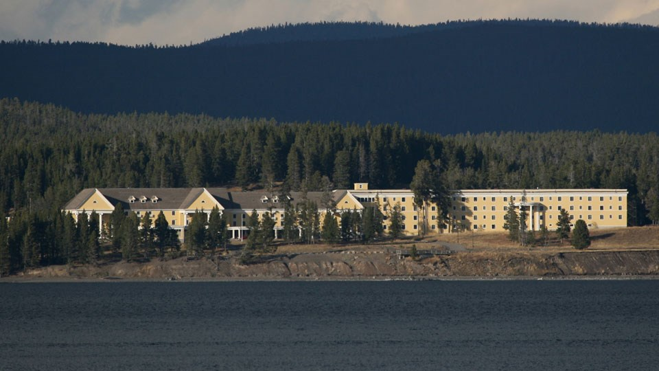 Yellow hotel building nestled in conifer forest next to the blue waters of Yellowstone Lake.