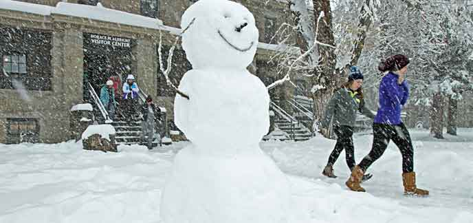 Snowman and people in front of a building during a snowstorm.