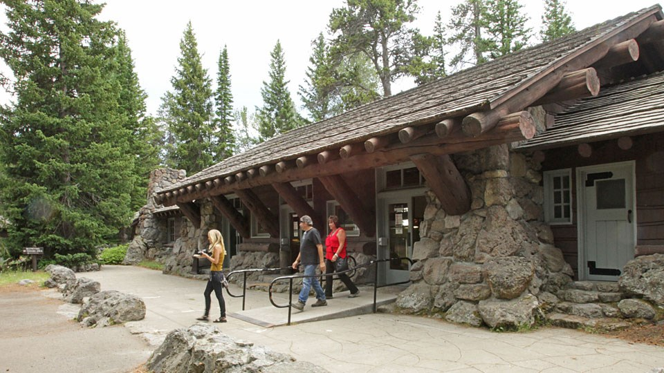 Three visitors leaving the single-story, stone and wood visitor center.