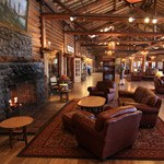 leather chairs and couch are located near a fireplace, in a large log-cabin style lodge room