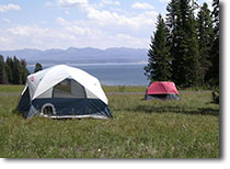 Campground with tents pitched with Yellowstone Lake in the background.