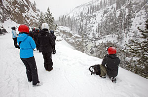 A group of visitors stands in front of the snow-covered scenery of Firehole Falls.