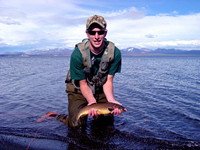 Angler kneeling in Yellowstone Lake and holding cutthroat trout with Absaroka Mountains in the background.