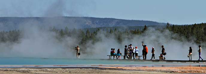 Visitors at Grand Prismatic experience the steam and bright colors of the spring while taking photos and pausing to sit on a bench.