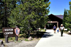 A ranger and visitors walk out of the Grant Village Visitor Center