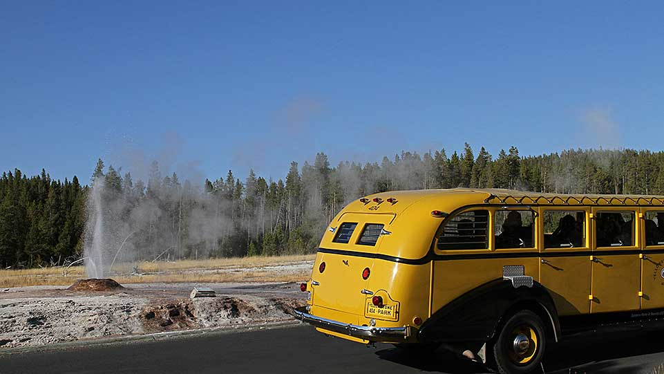 Tour bus passes by a geyser