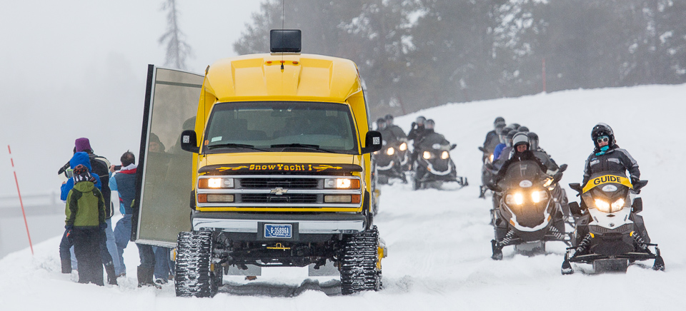 Snowmobiles pass by a snowcoach pulled over to let visitors view Midway Geyser Basin