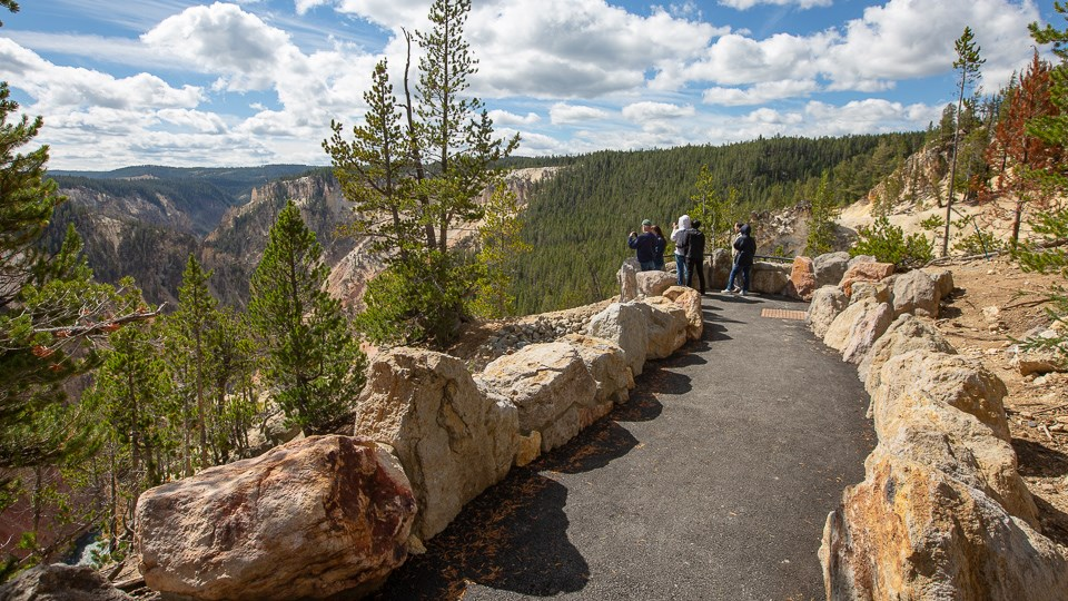 A paved walkway leads to an overlooks where people are looking into a canyon