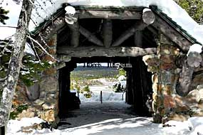 The large entrance to the Norris Museum with rock walls and large timbered rafters covered with spring snow.