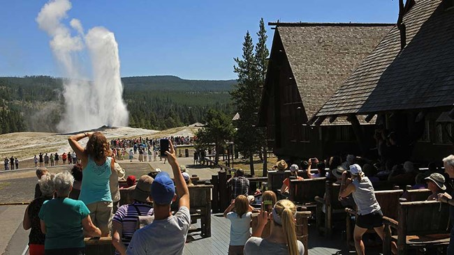 Crowd on an outdoor balcony watching a geyser erupt water and steam into the air.