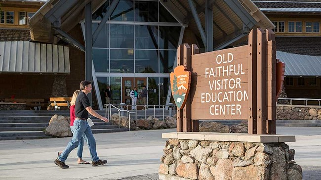 "Couple walks in front of a tall, glass-paneled building and behind a sign that reads ""Old Faithful Visitor Education Center""."