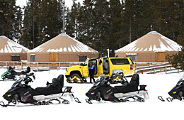 Snomobiles line up in a parking lot at Old Faithful during winter