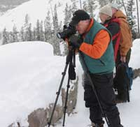 A photographer photographs the snowy landscape at Gibbon Canyon Overlook.