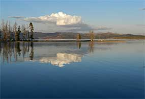 Yellowstone Lake with the sky and clouds reflected in the lake.