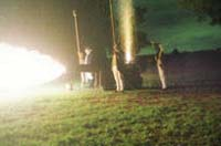 Color photograph of the firing of a cannon at night.