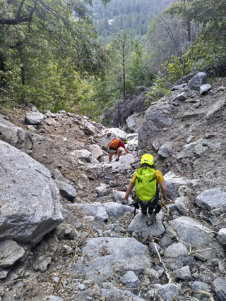 Rescuer and hiker descending steep canyon