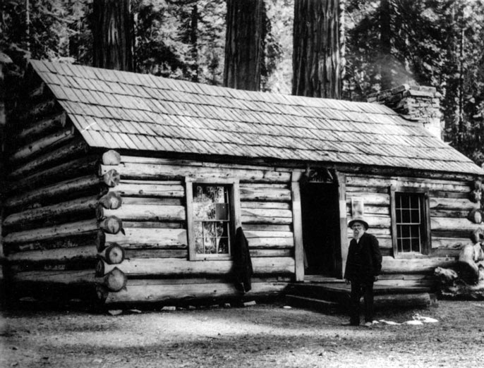 Galen Clark standing in front of a log cabin.
