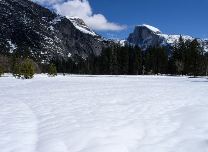 Half Dome and Yosemite Valley covered in white, fluffy snow.