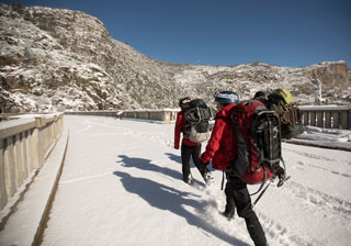 Hikers walking across snow-covered dam toward hills