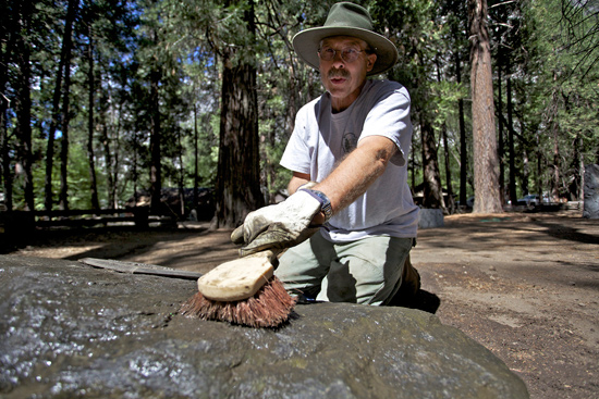 A volunteer scrubs the marker stone of Forest Townsley, Chief Ranger in Yosemite from 1916 until his death in 1943.