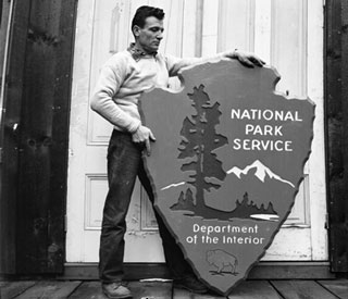 Man standing next to National Park Service arrowhead