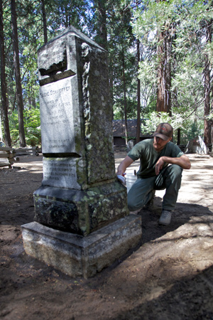 Volunteer cleans lichens and mosses from the headstone of Sadie Schaeffer, a local waitress who drowned in the Merced River in 1901.