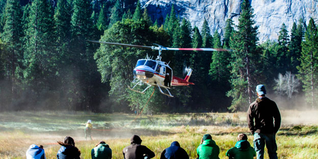 Helicopter lands in a meadow as people look on