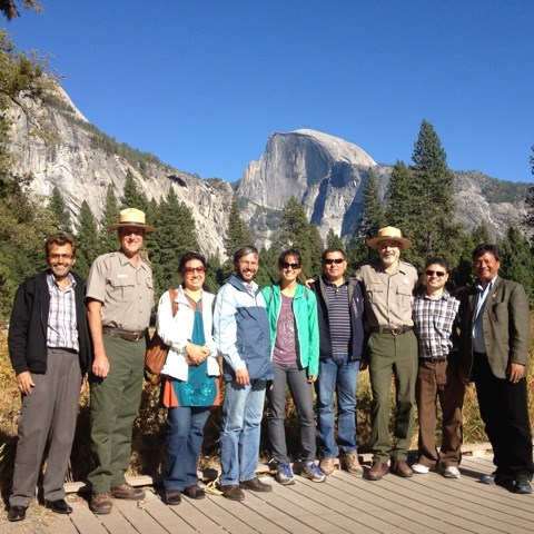 A delegation from Parks Nepal stand with NPS rangers with Half Dome in the background.