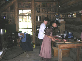 Young pioneers cooking in the Homestead Cabin.
