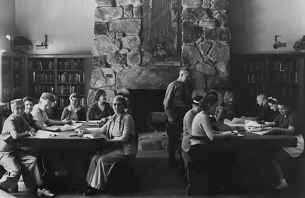 historical photograph of the Yosemite Museum Library with men and women studying.